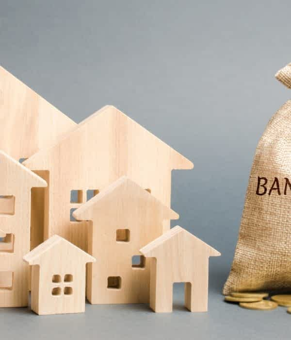 A money bag with the word Bankruptcy, a down arrow and wooden houses