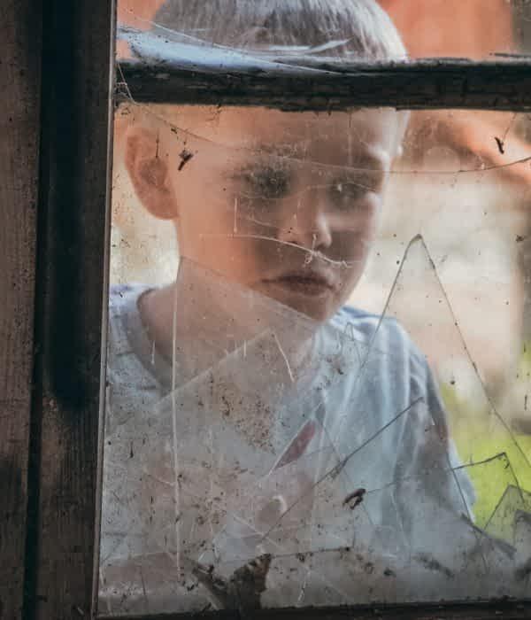 Boy looking through a broken window