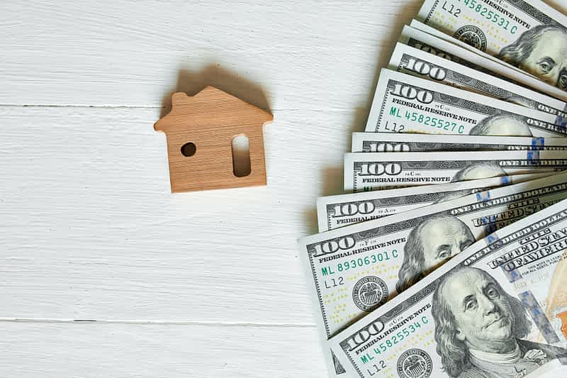 we buy houses for cash - Small wooden house and hundred dollar on white background