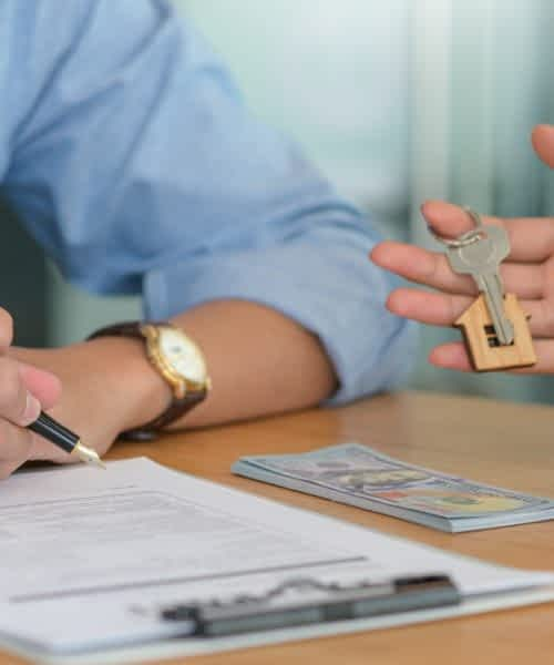 Signing a contract and delivering the house keys for buying and selling houses.